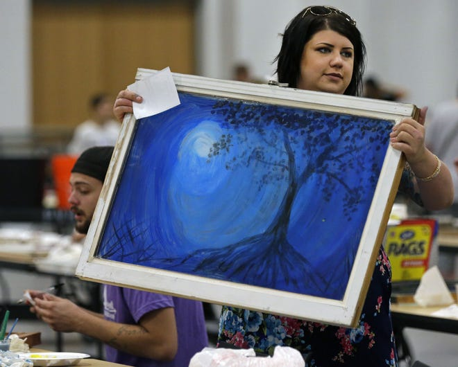 Kellie Johnson carries her finished window to be registered as she gathers with other painters Saturday to paint old windows for the Windows for a Cause fundraiser at the Fox Cities Exhibition Center.