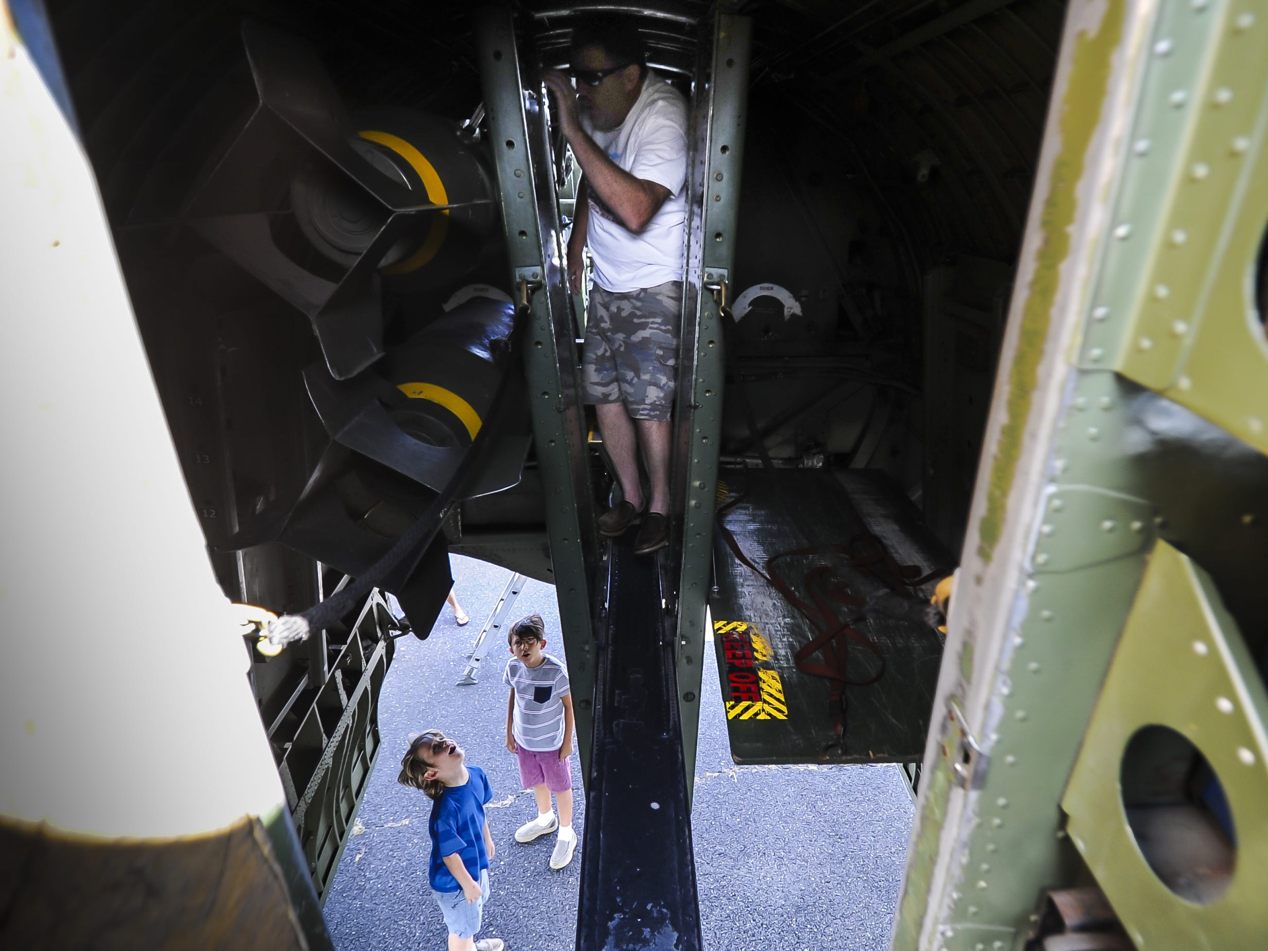 Jonathan Murath of Howell, center, walks across the plank inside the B-17 G Flying Fortess, as children look up at the bombs during the traveling WW II Wings of Freedom Tour exhibit at Momouth Jet Center/Executive Airport in Wall on Aug. 22, 2018.