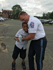 Marlboro police captain Pete Pezzullo embraces 10-year-old Jeremy Bristol.