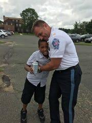 Marlboro police captain Pete Pezzullo embraces 10-year-old Jeremy Bristol.