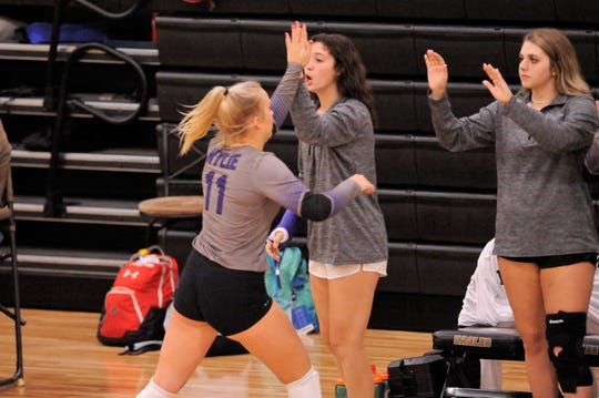 Wylie's Keetyn Davis gives teammate Lexie Miller (11) a high-five during Tuesday's match against Abilene High.