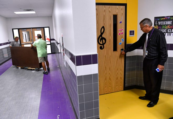 Superintendent Joey Light checks a classroom door as staff members wheel furniture down a hallway on Tuesday at Wylie East Elementary School. While the first day of school for Wylie ISD will be Monday, it will also be the new building's first day as a school, too.