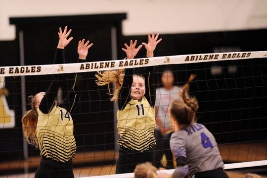 Abilene High's Sarah Cox (11) jumps to attempt a block during Tuesday's match against Wylie at Eagle Gym on Aug. 21, 2018. The Lady Eagles won 3-0.