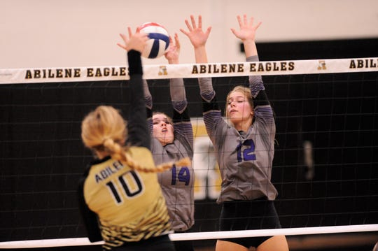 Wylie's Ginger Lanman (14) and Madison Burden (12) attempt a block during Tuesday's match against Abilene High's Saige McCray at Eagle Gym on Aug. 21, 2018. The Lady Eagles won 3-0.