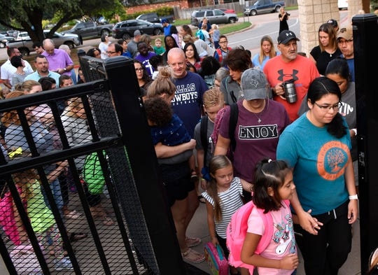 Parents and students enter Austin Elementary School Wednesday morning after the gate was opened for the first day of school.