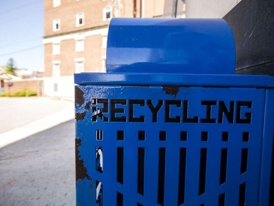The city of Asheville does own and service the blue recycling bins downtown and in West Asheville. They're usually paired with a black, metal garbage bin.