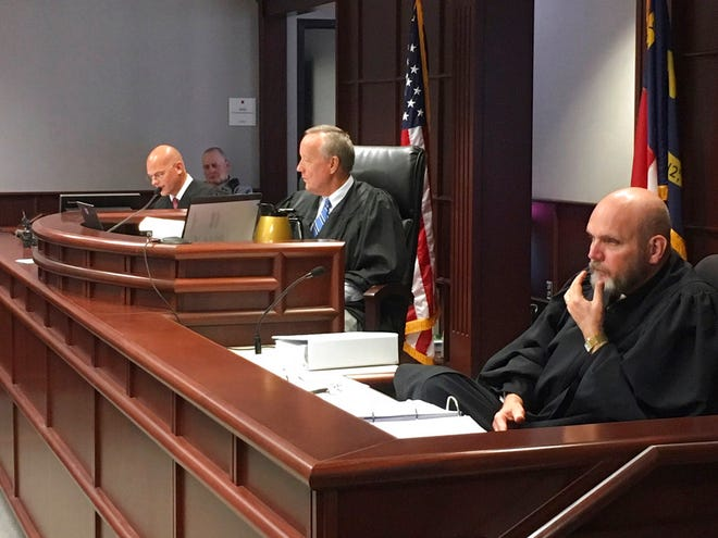 A trio of North Carolina judges in Raleigh, N.C., listen Wednesday, Aug. 15, 2018, as attorneys argue whether proposed amendments to the North Carolina constitution were worded to be misleading and mask the goal of Republican legislators to reduce Democratic Gov. Roy Cooper's powers. They are, from left, Superior Court Judges Jeffrey Carpenter of Union County, Forrest Donald Bridges of Cleveland County and Thomas Lock of Johnston County.