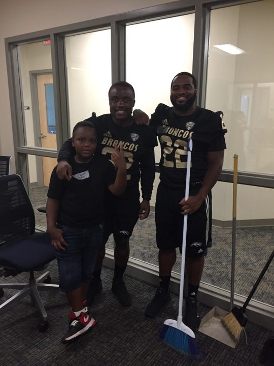 Western Michigan running backs Jamauri Bogan (32) and Davon Tucker (22) pose after helping clean Minnestry With Community in Kalamazoo as part of a team service project.