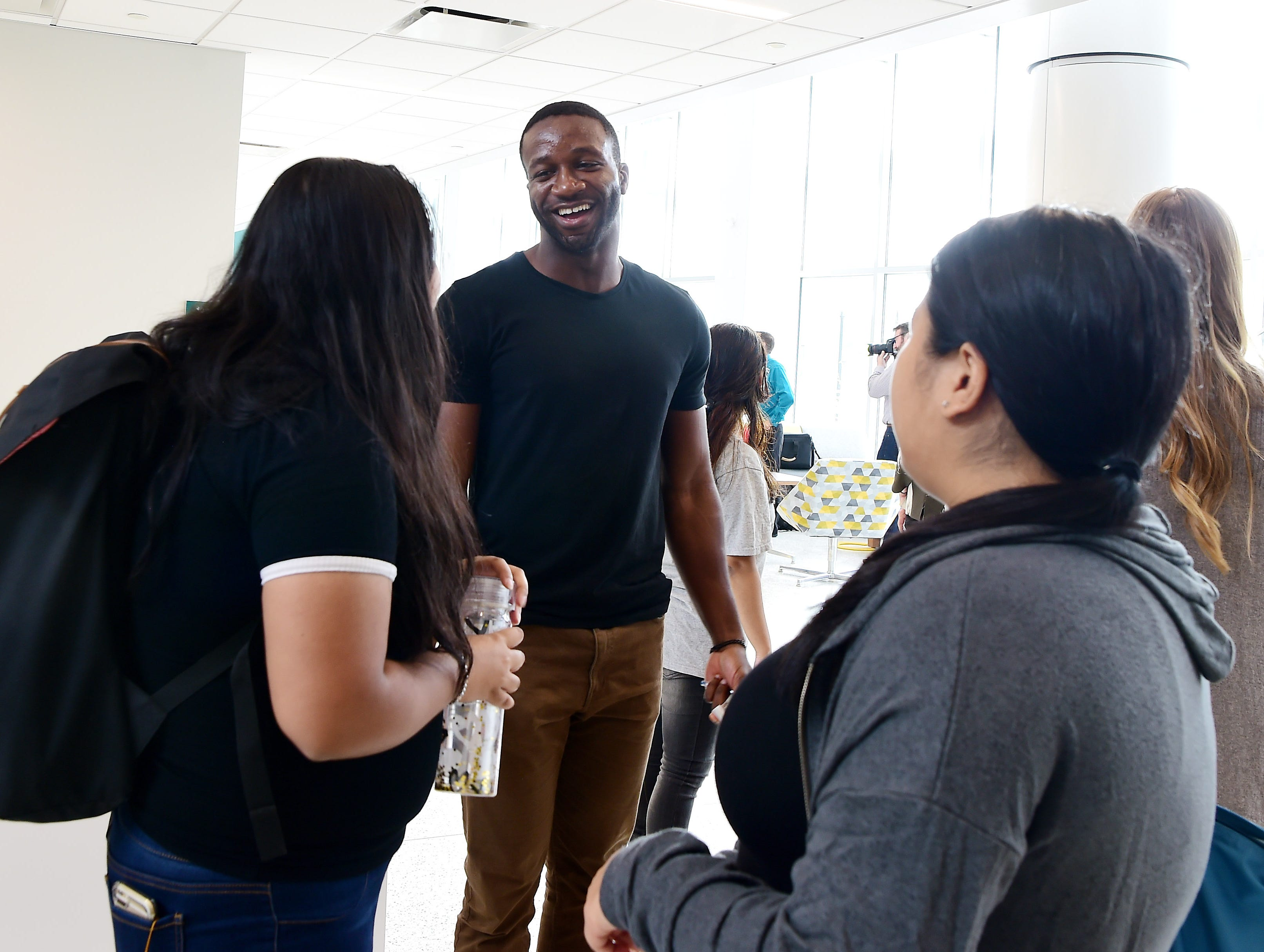 Biomedical engineering PhD student Ositomiwa Osipitan of Albany chats with friends during the first day of classes at Binghamton University's new School of Pharmacy and Pharmaceutical Sciences, which officially opened on Wednesday, August 22, 2018. The opening of the academic building at 96 Corliss Ave., Johnson City marks the first phase of the transformation of the former industrial section of Johnson City into the UniversityÕs Health Sciences Campus. Work will soon begin on the adjacent former Endicott Johnson shoe box factory, where the university will house its nursing program. Expected completion of the estimated $30 million renovation of the 48 Corliss Ave. nursing complex is August 2020. The School of Pharmacy and Pharmaceutical Sciences will have approximately 390 students when fully enrolled after four years Ð 360 in the PharmD program and an additional 30 PhD students.