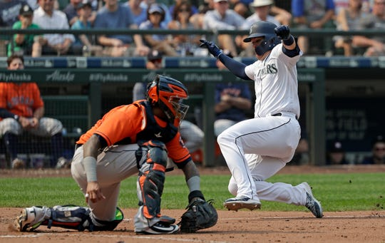 Mariners first baseman Ryon Healy slides past Astros catcher Martin Maldonado to score during Houston's 10-7 win on Wednesday in Seattle.