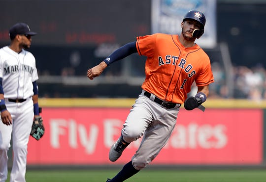 Carlos Correa of Houston races past Seattle Mariners third baseman Robinson Cano to score in the first inning of Wednesday's game.