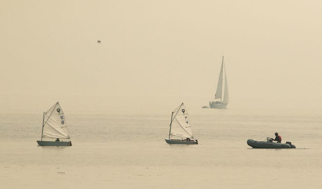 Sailboats head for the Kingston Marina on a smokey and hazy Wednesday August 15, 2018.