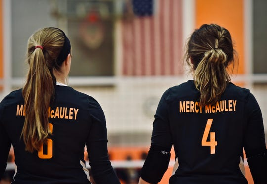 Mercy McAuley's Rachel Berwanger and Nicole Berlanger join arms for the National Anthem prior to the first home volleyball match for the Wolves Tuesday, August 21st at Mercy McAuley High School