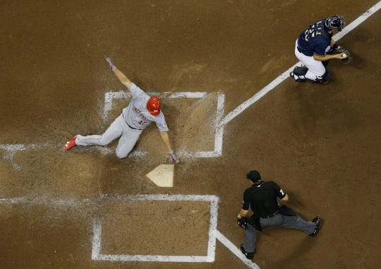 Cincinnati Reds' Sal Romano scores past Milwaukee Brewers catcher Erik Kratz during the third inning of a baseball game Tuesday, Aug. 21, 2018, in Milwaukee.