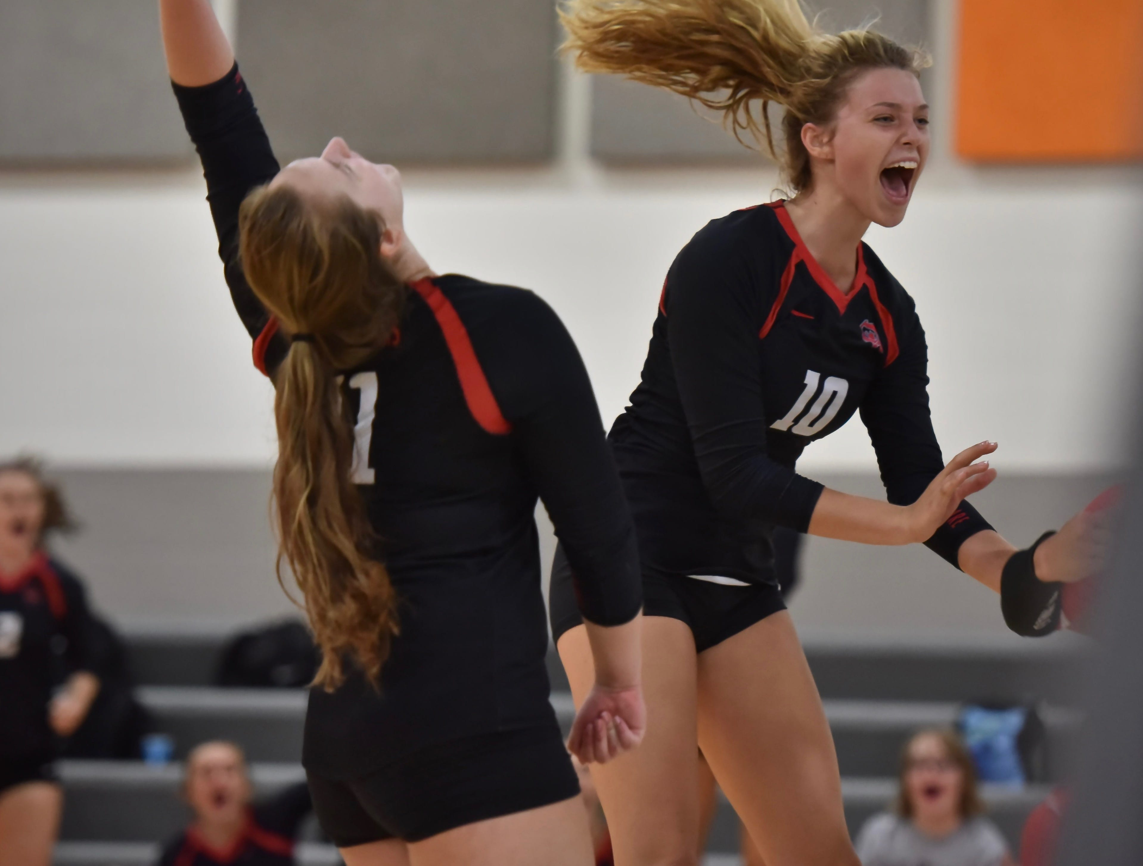Oak Hills' Abigail Hulsman and Kasey Bryant celebrate the Highlanders first set victory over Mercy McAuley Tuesday, August 21st at Mercy McAuley High School