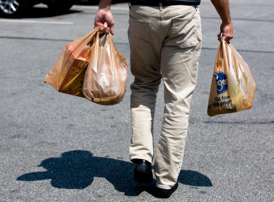 A customer carries their items from Kroger to their car in plastic bags in Newport, Ky., on Wednesday, Aug. 22, 2018.