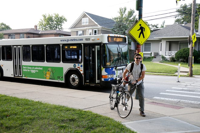 Commuter Wade Johnston, 28, of Mt. Washington, removes his bike from the rack of the No. 24 bus at his stop near the intersection of Michigan and Observatory in the Hyde Park neighborhood of Cincinnati on Wednesday, Aug. 22, 2018. Johnston splits his daily commute from Mt. Washington to Madisonville between the Metro bus and his bicycle.