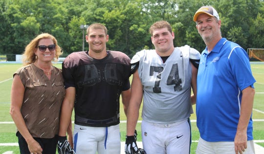 Chris. far right, and Renee, far left, Kandra join their sons at their scrimmage Aug. 18 when Mount St. Joseph (Evan, second from left) took on Thomas More College (Evan, second from right).