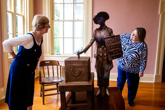 Ellen Kanervo and Brenda Harper, right, examine a cut out of the Clarksville suffragist statue at the Smith-Trahern Mansion Wednesday, Aug. 22, 2018, in Clarksville, Tenn.