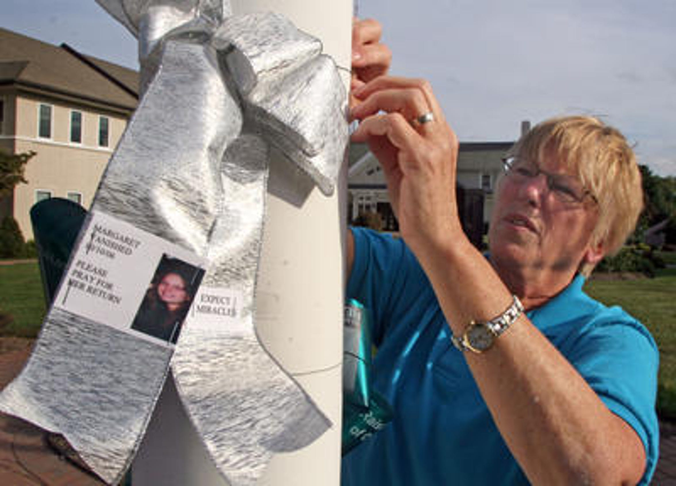 Eileen Haddican mother of Margaret Haddican-McEnroe ties a ribbon with a photo of her daughter at the Warren municipal complex. Ribbons are hung around the area each year marking the October 10, 2006 anniversary of Haddican-McEnroe's disappearance.