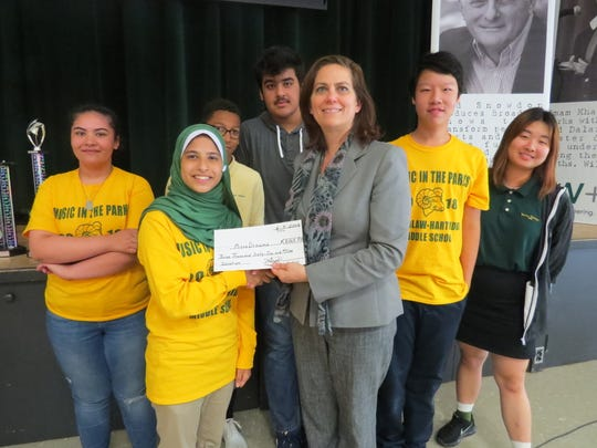 Dr. Corinna Crafton of Edison, Middle School Head, receives a check for the MicroDreams Foundation from eighth grade student Faizah Naqvi of South Plainfield. Looking on, from left: Madison Torres of Edison, Kori Brown of Plainfield, Shiv Tickoo of Scotch Plains, Robin Zhong of Edison and Tiffany Yu of Roselle.