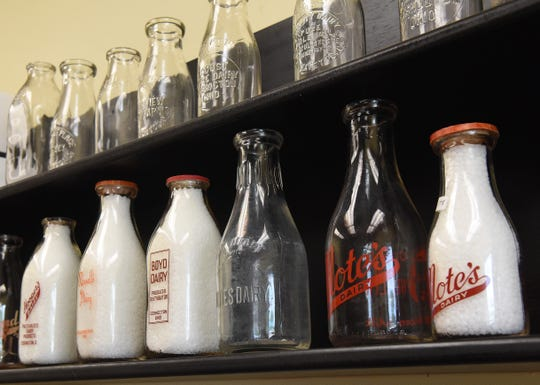 Antique milk delivery bottles from local diaries on display in a conference room at Pearl Valley Cheese.