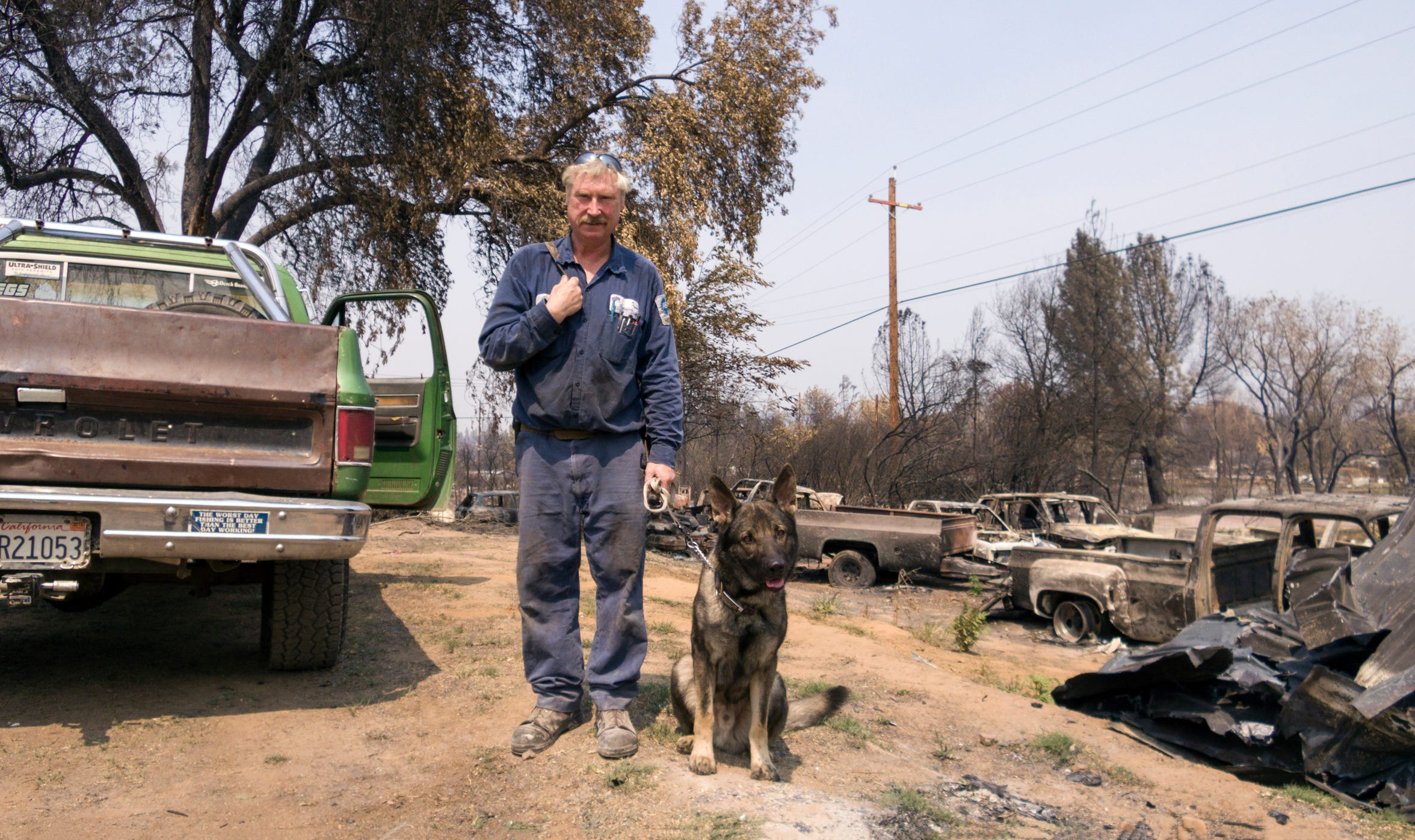John J.J. Johnson, 53, who lost his rental home, $40,000 in tools and 14 cars from the tornado fire tries to salvage what he can with his dog Max in Keswick, Calif., Monday, August 20, 2018.