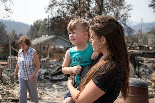 """From right, Dorene Leach, 31, son Waylon Hutchens, 3 and her grandmother Bonnie Fruits look through the debris of her burned home in Keswick, Calif., Monday, August 20, 2018.  The burn pile made it through the fire.  """"It's like a cruel joke,"""" said Leach."""