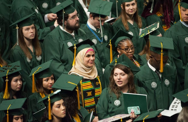 Graduates look around for their family members in the audience at the start of Eastern Michigan University's spring commencement at the Convocation Center in Ypsilanti on Saturday, April 21, 2018. (John T. Greilick, The Detroit News)
