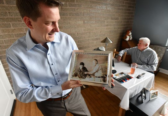Dan Kosmowski holds a 1967 photo of his father, Bernie, while in the military in the Vietnam War, receiving a Purple Heart after getting injured while in the artillery.