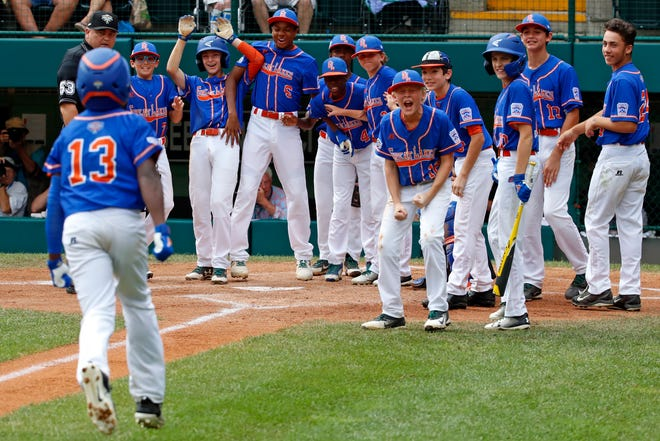 Grosse Pointe Woods-Shore's Oliver Service is greeted by teammates after a home run in Wednesday's elimination game of the Little League World Series.