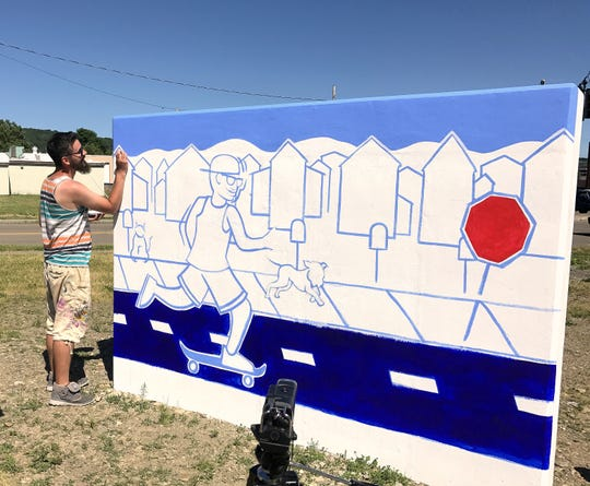 Artist Brad Leiby works on a mural earlier this summer outside the Community Arts of Elmira building on Lake Street.