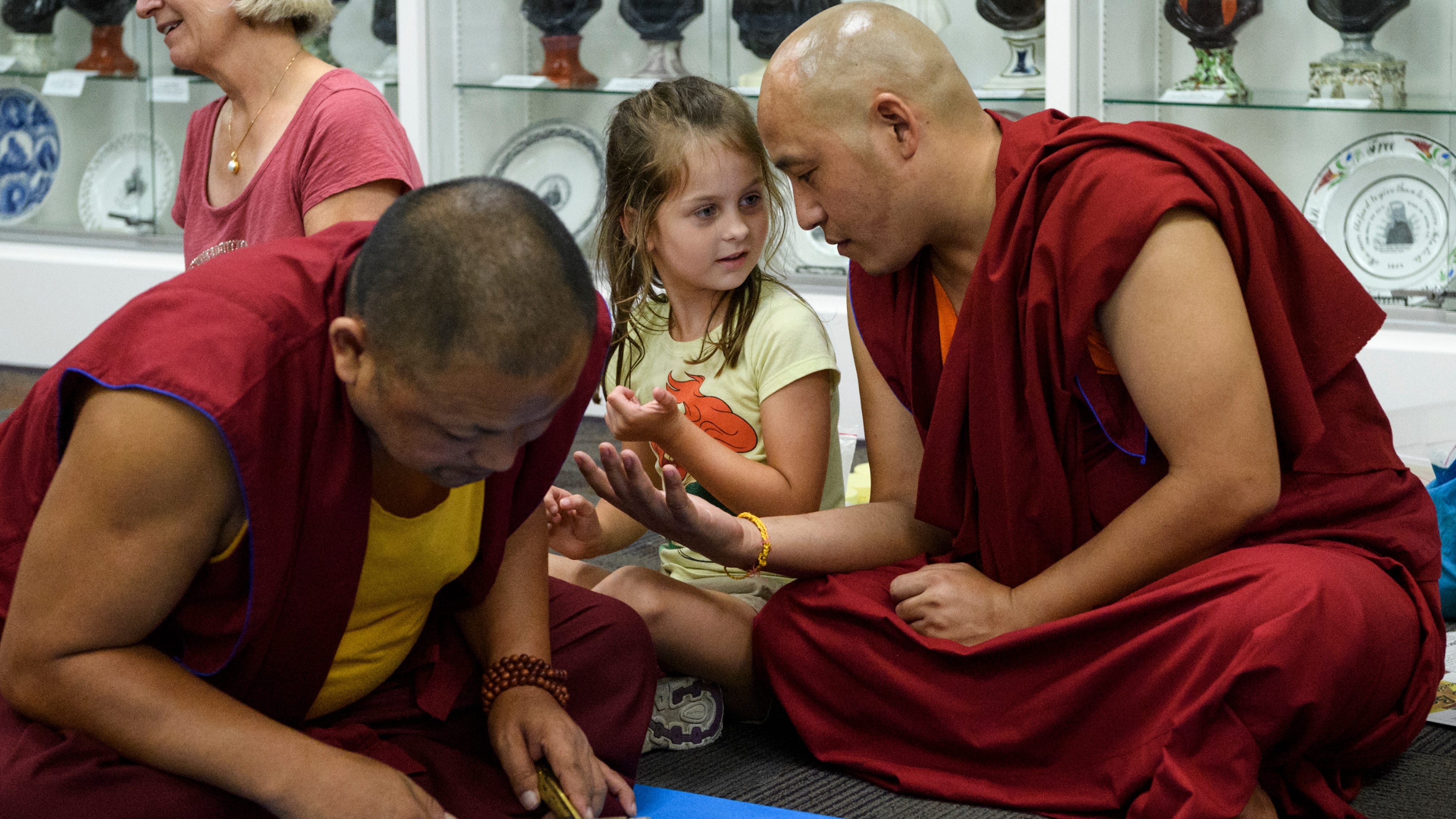 Ayla Martin, 6, center, and Yeshi Rabgyal, right, a monk visiting from Tashi Kyil Monastery in Dehra Dun, India, compare the size of each other's hands as Kalsang Jinpa, left, works on a World Peace Sand Mandala inside the John Wesley Gallery in the basement of Neu Chapel at the University of Evansville, Monday evening, Aug. 20, 2018. Martin's grandmother Cecile Martin, back left, has coordinated the monks past three trips to Evansville and introduced Rabgyal to Martin when she was only 6-months-old.