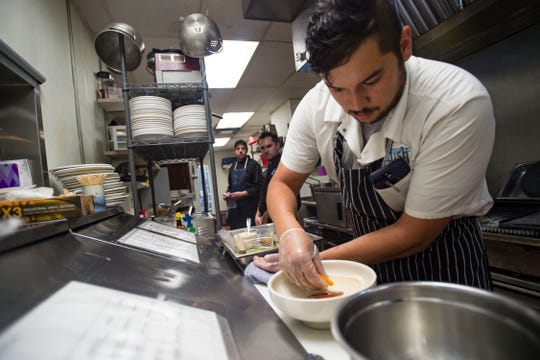 Chef de cuisine Ryan Damasky prepares a dish of seared Maine scallops on a bed of heirloom tomatoes, an herb flower medley, and blue pickled garlic with a black vinegar creama sauce on Wednesday, Aug. 15, 2018, at Fish Restaurant in Old Town Fort Collins, Colo.