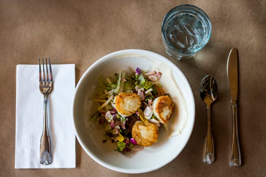 Seared Maine scallops on a bed of heirloom tomatoes, an herb flower medley, and blue pickled garlic with a black vinegar creama sauce is prepared by chef de cuisine Ryan Damasky on Wednesday, Aug. 15, 2018, at Fish Restaurant in Old Town Fort Collins, Colo.