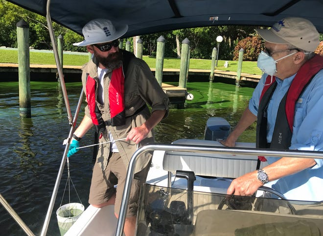 Dr. James Metcalf, left, prepares to dip a sampling bag into a North Fort Myers area with an active toxic algae bloom. Calusa Waterkeeper John Cassani piloted the scientist to areas along the river to take water samples.