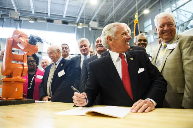 Gov. Henry McMaster laughs before ceremoniously signing a bill at Greenville Technical College's Center for Manufacturing Innovation on Wednesday, Aug. 22, 2018. The event was held to celebrate a new bill that passed in June that allows technical colleges to offer a four-year degree in advanced manufacturing technology.