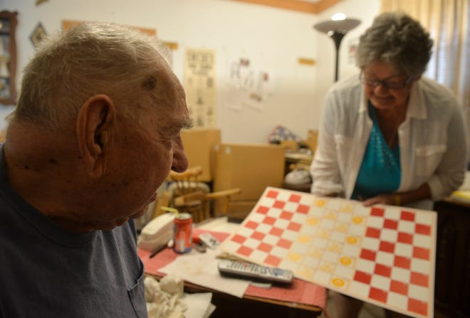 Ed Bucko, who turned 104 years old recently, looks to Sharon Schock who shows off a King Check game board.  Bucko invented the King Check game in the late 60's and hopes to revive its sales with the help of Schock.