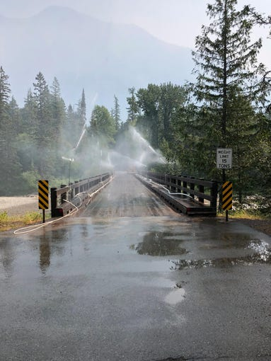 Firefighters are using a sprinkler system to protect a Glacier National Park bridge from the Howe Ridge Fire.