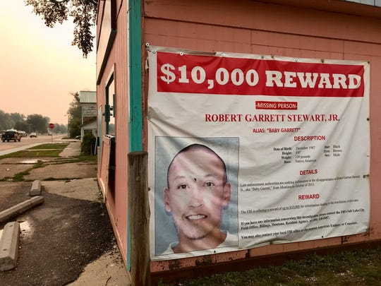 A banner offering a reward for information on a missing Montana man hangs on a laundromat wall in Crow Agency
