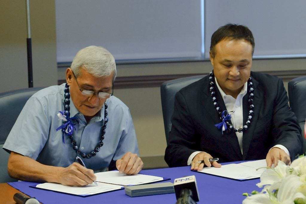 In this August 2018 file photo, Guam Power Authority General Manager John Benavente, left, signs a contract with Hanwha Energy for a 60 megawatt solar plant. Hanwha, which also bid on the island's new 180 megawatt power plant, has protested the decision to award the contract to Korea Electric Power.