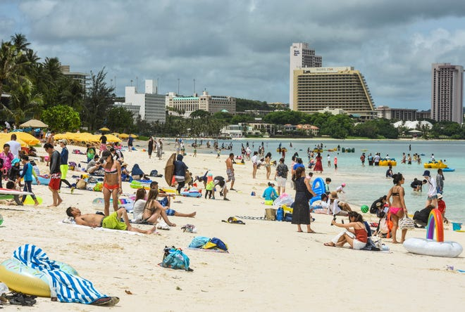 Visiting tourists and other beachgoers take to the sand and water of Tumon Bay as the sun peers out from the clouds in this Aug. 22, 2018, file photo.
