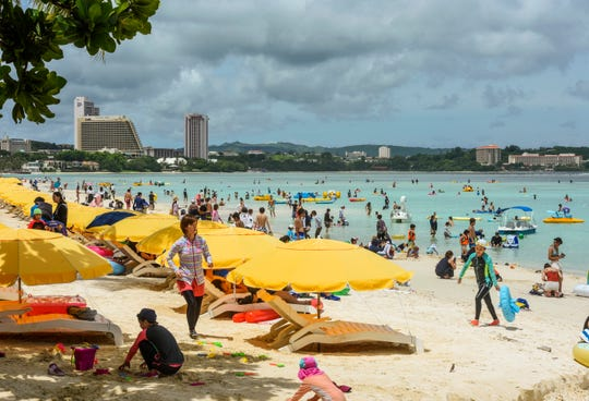 Visiting tourists and other beachgoers take to the sand and water of Tumon Bay as the sun peers out from the clouds above on Wednesday, Aug. 22, 2018.