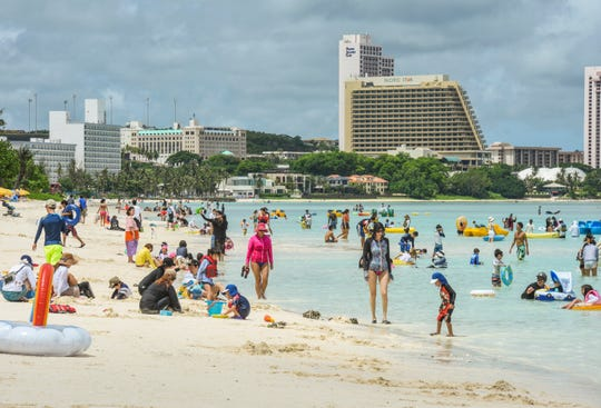 Visiting tourists and other beachgoers take to the sand and water of Tumon Bay as the sun peers out from the clouds above on Wednesday, Aug. 22, 2018. Property improvements or buildings worth $1 million or more, including those in the tourist district of Tumon, have been assessed a higher tax.
