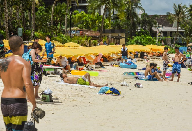 Visiting tourists and other beachgoers take to the sand and water of Tumon Bay in this Aug. 22 file photo.