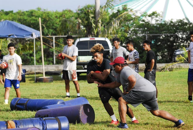 George Washington Geckos players run through ball-carrying drills as head coach Ryan Rios attempts to dislodge the ball during practice at the school campus on Aug.15.