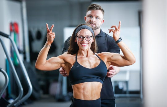 Rachael Heffner practices a front double biceps bodybuilding pose in the mirror under the supervision of her Body Building Coach and owner of Arc Fitness, Adam Cayce, at ARC Fitness Indy on Tuesday, Aug. 21, 2018. Heffner went from weighing 300 pounds in 2011 to becoming the 2018 NPC Indiana State Championships Women's Open Physique Overall Champion.