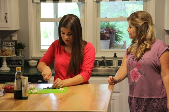 Tori (Bates) Smith and Erin (Bates) Paine cook together at Erin's home.
