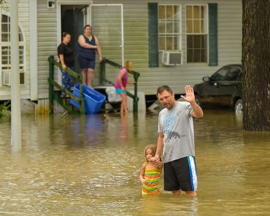 A family wades through Lafayette Parish floodwaters in August 2016.