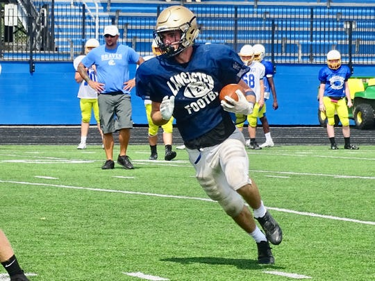 Lancaster senior A.J. Cook runs the ball during a scrimmage against Olentangy. The Golden Gales open the season at Springfield on Friday.
